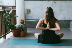 Fitness im Homeoffice, junge Frau macht Yoga